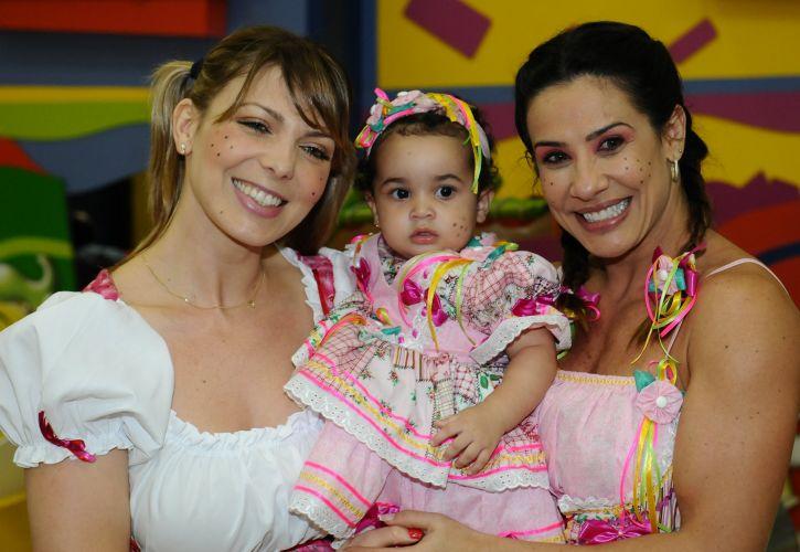 Vestida de caipira, Scheila Carvalho comemora o aniversário de 1 ano da filha Giulia, ao lado da ex-companheira do grupo