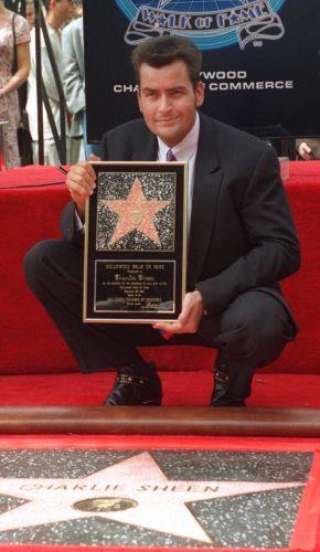 O ator Charlie Sheen entra para a Calçada da Fama e posa ao lado de sua estrela (1994)