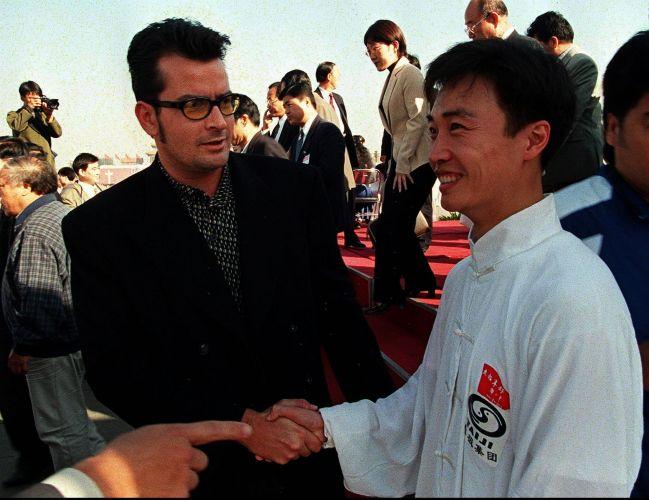 Charlie Sheen encontra-se com um dos participantes da apresentação de artes marciais na praça Tiananmen, em Pequim