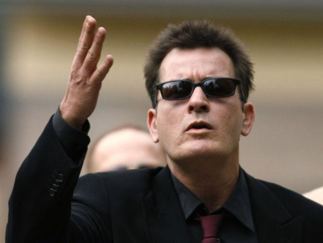 Ator Charlie Sheen faz gestos para os fãs, após sair de uma audiência. Os fãs não gostaram de seu show e gritavam