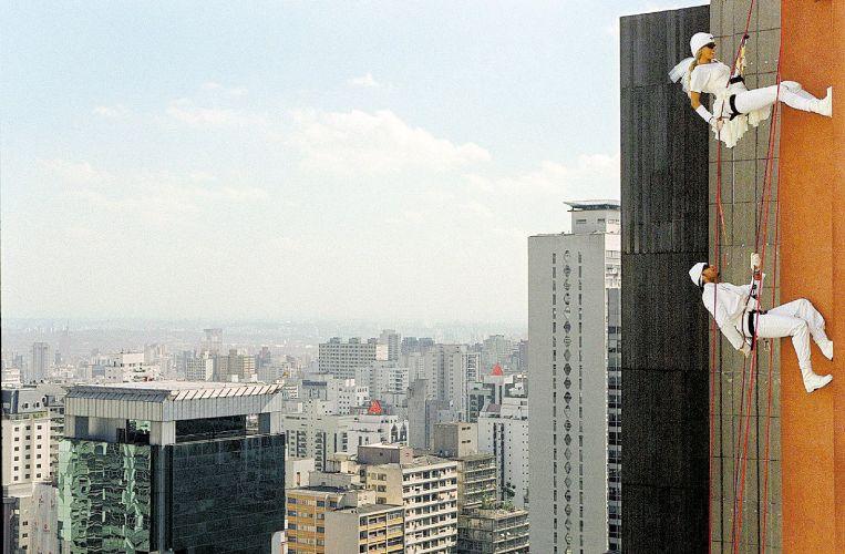 Vestida de noiva, Adriane e o cantor mexicano Jaime Camil, seu namorado na época, fazem rapel em prédio da avenida Paulista, em São Paulo, para campanha publicitária de uma marca de sabão em pó (15/5/03)