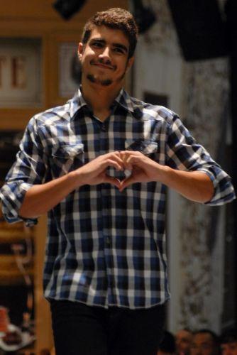 O ator Caio Castro faz um coração com a mão para uma fã durante evento de moda em São Paulo (16/5/10)