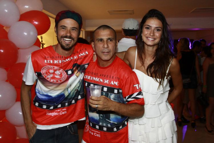 O casal Paulinho Vilhena e Thaila Ayala posa junto ao aniversariante, Eri Johnson, ao chegar para a festa em comemoração aos 50 anos do ator, no sábado, na quadra do Salgueiro (18/12/2010)