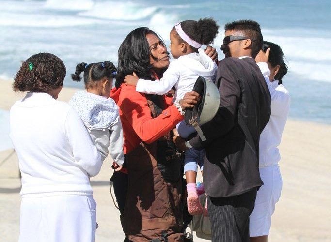 Após saltar de asa delta, Gloria Maria abraça as filhas Laura e Maria, no Rio de Janeiro (3/9/11)