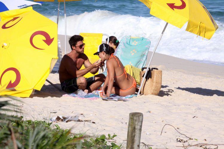 Juliana Paes ganha um pedacinho do lanche do marido, Carlos Eduardo Baptista, na tarde de sábado. O casal descansou nas areias da Barra da Tijuca, Rio de Janeiro (1/5/2010)