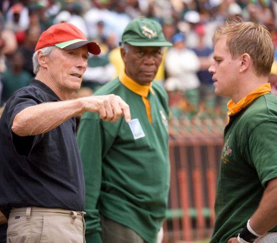 Matt Damon ouve as dicas do diretor Clint Eastwood (esq.) em cena com Morgan Freeman (centro) durante gravação do filme