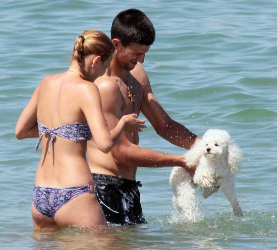 O tenista profissional sérvio Novak Djokovic, o novo campeão do torneio de Wimbledon, e a namorada de longa data, Jelena Ristic, curtem um dia na praia em Saint Tropez, no sul de França. Nem o cachorrinho poodle ficou de fora (15/7/11)