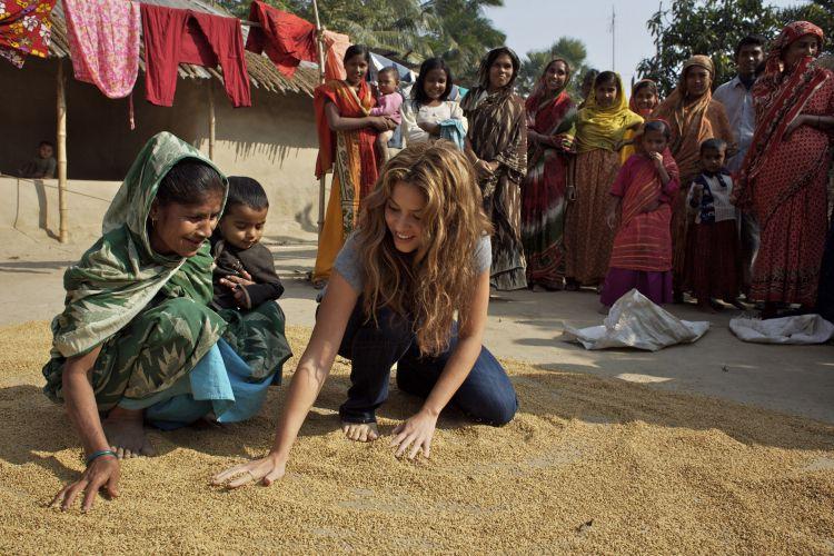 Embaixadora da UNICEF, Shakira aprende com uma mulher como as mulheres processam os grãos de arroz, em Modhu Shudanpur, em Bangladesh (19/12/2007). De 17 a 19 de novembro, a cantora colombiana passou por diversas vilas do litoral afetadas por um ciclone que atingiu o país no dia 15 de novembro de 2007