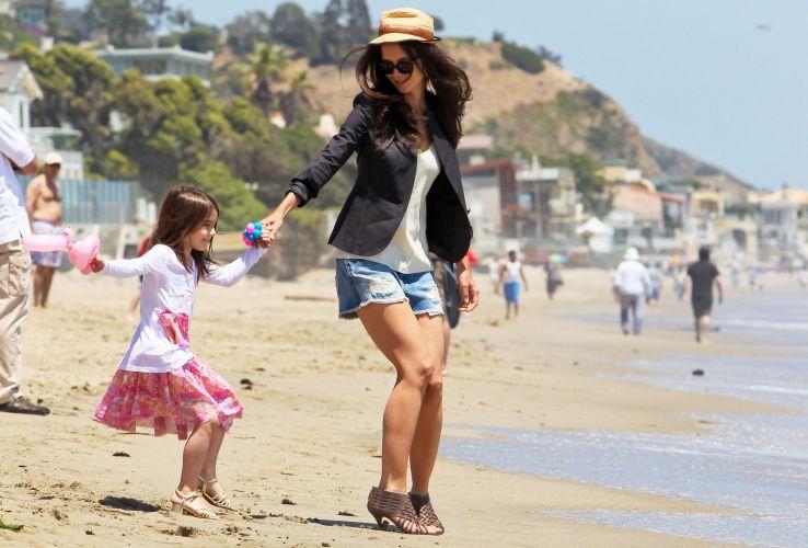 Usando salto, Suri Cruise e Katie Holmes têm dificuldade em andar na areia da praia, em Malibu (30/5/2011)