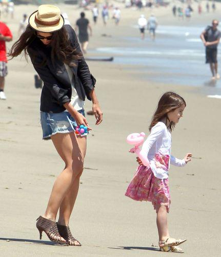 Katie Holmes observa o estado do sapato de salto enquanto brinca com a filha em praia de Malibu (30/5/2011)
