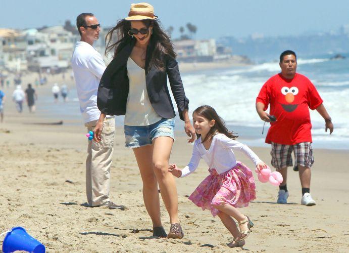 De salto, Suri Cruise corre em praia de Malibu, acompanhado da mãe Katie Holmes (30/5/2011)