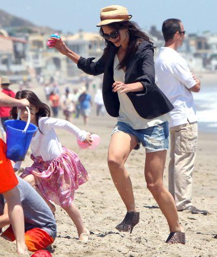 De salto, Katie Holmes se preocupa em não cair na areia enquanto corre atrás da filha Suri, que também usa um salto, em praia de Malibu (30/5/2011)