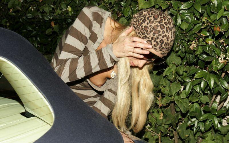 Paris Hilton deixa o seio à mostra enquanto olha o estado de seu carro, após uma pequena batida (8/1/2007)