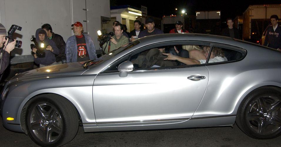 O então namorado de Paris, Stavros Niarchos, cobre a cabeça, após bater o carro da socialite na saída de um clube noturno em Hollywood (8/11/2005). Após conversarem com a polícia, o grupo seguiu para uma festa em um hotel da cidade