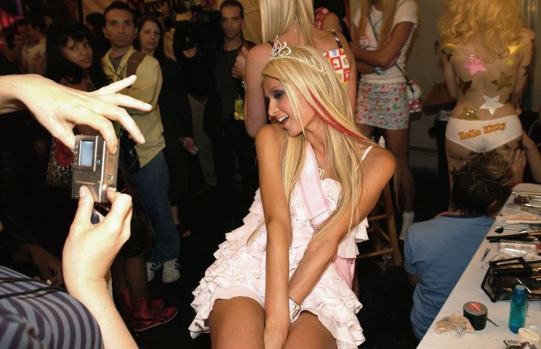 Paris Hilton faz pose para um fã durante desfile na semana de moda de Los Angeles (2/4/2003)