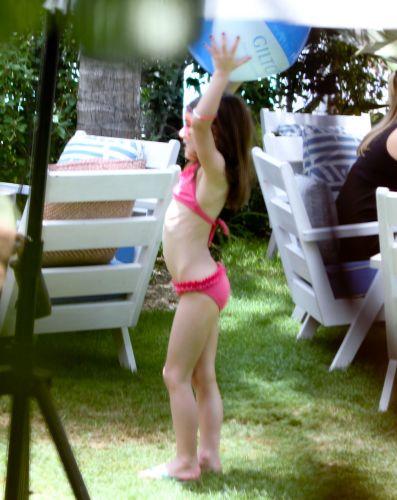 De biquíni rosa, Suri brinca com uma bola ao redor da mesa onde seus pais conversam, durante a comemoração dos 49 anos de Tom Cruise, no Soho Beach House Miami Hotel em Miami, na Flórida (3/7/11)