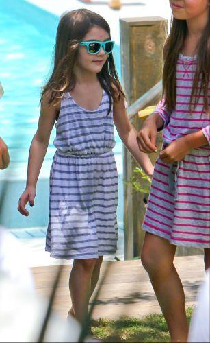 Ainda sem cara pintada, Suri chega à piscina de óculos escuros combinando com seu vestido, durante a comemoração dos 49 anos de Tom Cruise, Soho Beach House Miami Hotel em Miami, na Flórida (3/7/11)