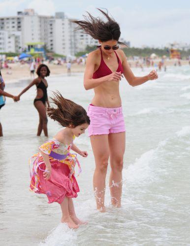 Suri Cruise pula uma onda ao lado da mãe Katie Holmes, em Miami (18/6/2011)